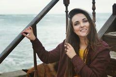 Mujer morena sonriente hermosa que sienta en las escaleras contra paisaje marino, sonriendo y mirando la cámara Fotografía de archivo libre de regalías