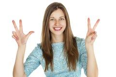 Mujer morena sonriente joven que muestra la victoria o el signo de la paz Imagenes de archivo