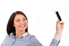 Mujer morena sonriente joven que toma un selfie Imagenes de archivo