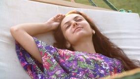 Mujer morena sonriente joven relajada en hamaca en la playa tropical Cierre para arriba metrajes