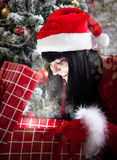 Mujer morena sorprendente que abre un presente por completo de la magia de la Navidad Imagenes de archivo