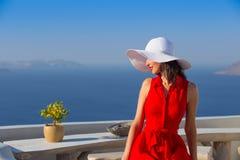 Mujer morena turística del viaje de Santorini en vestido rojo que visita el pueblo blanco famoso de Oia imágenes de archivo libres de regalías