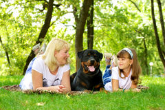 Mujer, muchacha y perro en la hierba. Fotografía de archivo