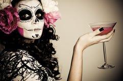 Mujer muerta de vida de Víspera de Todos los Santos que tiene una bebida Fotografía de archivo