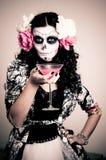 Mujer muerta de vida de Víspera de Todos los Santos que tiene una bebida fotos de archivo libres de regalías