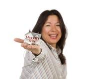 Mujer multiétnica atractiva que sostiene la pequeña casa Imagenes de archivo