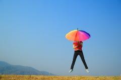 Mujer multicolora del paraguas que salta al cielo Imagenes de archivo