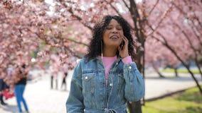 Mujer multirracial que escucha la música en un parque, árbol de las flores de cerezo alrededor almacen de metraje de vídeo