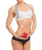 Mujer muscular con la manzana y la cinta métrica Fotografía de archivo libre de regalías