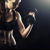 Mujer muscular deportiva con la elaboración con pesas de gimnasia Imágenes de archivo libres de regalías