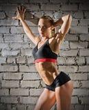 Mujer muscular en la pared de ladrillo gris (versión normal) Imagenes de archivo