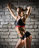 Mujer muscular en la pared de ladrillo gris (versión oscura) Fotos de archivo