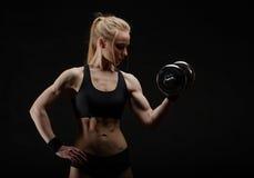Mujer muscular fuerte delgada joven que presenta en estudio con pesa de gimnasia Foto de archivo libre de regalías