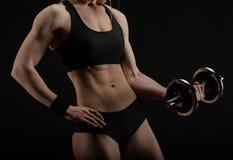 Mujer muscular fuerte delgada joven que presenta en estudio con pesa de gimnasia Imagen de archivo libre de regalías