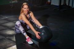 Mujer muscular hermosa del ajuste con la bola del crossfit, pared de ladrillo gris en el fondo Ajuste de la cruz fotografía de archivo