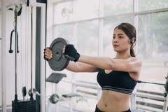 Mujer muscular hermosa del ajuste que ejercita los músculos del edificio y a la mujer de la aptitud que hacen ejercicios en el gi fotos de archivo
