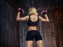 Mujer muscular hermosa que hace ejercicio con pesas de gimnasia en un gris Imagen de archivo libre de regalías