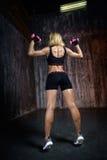 Mujer muscular hermosa que hace ejercicio en un fondo gris Fotografía de archivo libre de regalías
