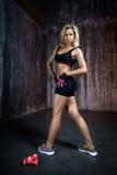 Mujer muscular hermosa que hace ejercicio en un fondo gris Foto de archivo