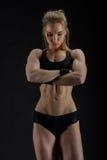 Mujer muscular joven que presenta en negro Imagenes de archivo