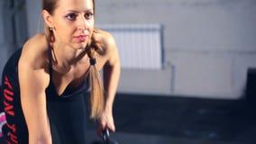Mujer muscular que ejercita fila de la pesa de gimnasia en el gimnasio almacen de video