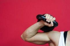 Mujer muscular que lleva a cabo el kettlebell Foto de archivo