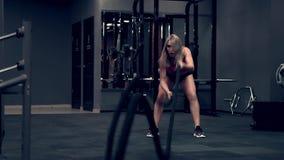 Mujer muscular que se resuelve en los pesos de elevación del gimnasio
