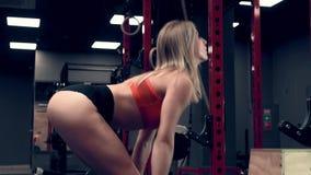 Mujer muscular que se resuelve en los pesos de elevación del gimnasio metrajes