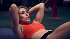 Mujer muscular que se resuelve en los pesos de elevación del gimnasio almacen de metraje de vídeo