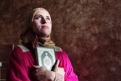 Mujer musulmán árabe con el hijab que lleva del libro sagrado del koran Fotos de archivo libres de regalías