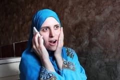 Mujer musulmán árabe sorprendida feliz con el móvil Foto de archivo libre de regalías