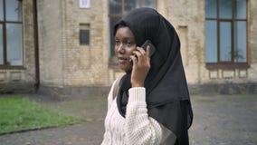 Mujer musulmán africana joven encantadora en hijab que habla en el teléfono celular y que camina en parque cerca de la universida almacen de video
