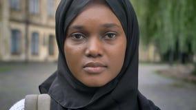 Mujer musulmán africana joven triste en el hijab que mira la cámara y la situación en parque cerca de universidad, serio y en cue metrajes