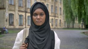Mujer musulmán africana triste joven en el hijab que mira la cámara y la situación en parque cerca de la universidad, subrayada y metrajes