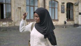 Mujer musulmán afroamericana joven en hijab que camina en parque cerca de universidad y que agita alguien, feliz y alegre almacen de metraje de vídeo