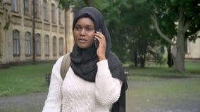 Mujer musulmán afroamericana joven en hijab que camina en parque cerca de universidad y que habla en el teléfono almacen de metraje de vídeo