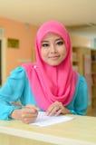 Mujer musulmán asiática joven en la sonrisa principal de la bufanda mientras que pluma de tenencia Imagen de archivo