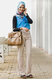 Mujer musulmán bastante joven con el teléfono y el bolso Fotos de archivo libres de regalías