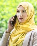Mujer musulmán bastante joven que tiene una conversación sobre el teléfono Foto de archivo