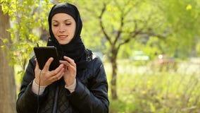 Mujer musulmán con una tableta en sus manos al aire libre Vídeo completo de HD almacen de video