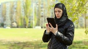 Mujer musulmán con una tableta en sus manos al aire libre Vídeo completo de HD metrajes