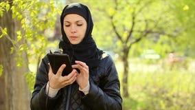 Mujer musulmán con una tableta en sus manos al aire libre Vídeo completo de HD almacen de metraje de vídeo