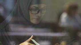 Mujer musulmán elegante en el libro de lectura de las lentes, preparándose para los exámenes de entrada almacen de metraje de vídeo