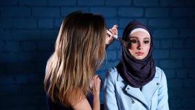 Mujer musulmán en hijab en salón de belleza Beautician que aplica maquillaje almacen de metraje de vídeo