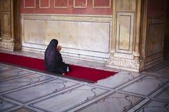 Mujer musulmán en sari que se arrodilla y que ruega en el m Fotos de archivo libres de regalías