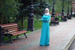 Mujer musulmán en vestido oriental y el pañuelo blanco en su cabeza en el parque Foto de archivo