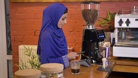 Mujer musulmán encantadora joven en el hijab violeta que hace el pago sin contacto por el teléfono celular y que le toma el café, almacen de video