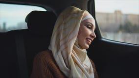 Mujer musulmán feliz que disfruta de paseo del taxi en la ciudad almacen de video