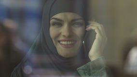 Mujer musulmán feliz que habla en el teléfono, tarifas favorables del operador móvil metrajes