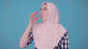 Mujer musulmán hermosa joven con una píldora y un vaso de agua que toman una píldora almacen de video